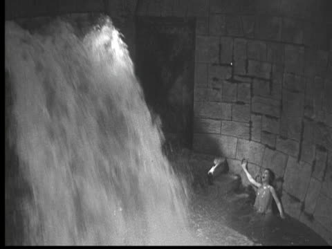 vídeos de stock e filmes b-roll de 1925 ms b/w water falling into dungeon, terrified woman screaming - 1925