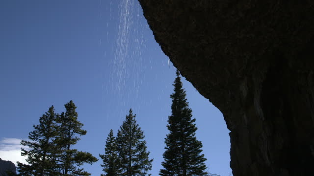 vídeos de stock, filmes e b-roll de water falling off cliff, shot from underneath - bozeman