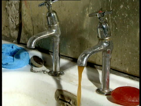 vidéos et rushes de water faucet tap turned on; brown water pouring out. water pollution on august 04, 1989 - eau robinet