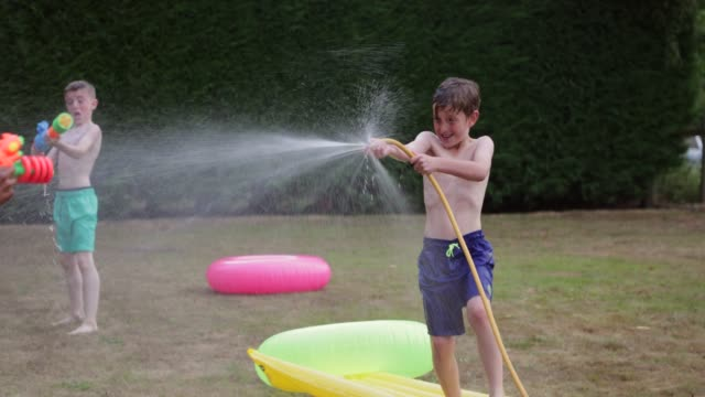 water fight in the back yard - water fight stock videos & royalty-free footage