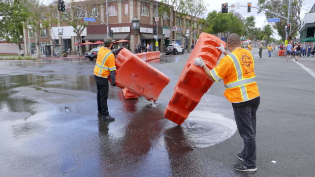 Water filled security road barriers blocks are being uninstalled by maintenance workers after street public event in Los Angeles, California, 4K