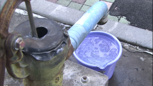 water fills a bucket under the spout of an old fashioned water pump in old town tokyo. - pour spout stock videos & royalty-free footage