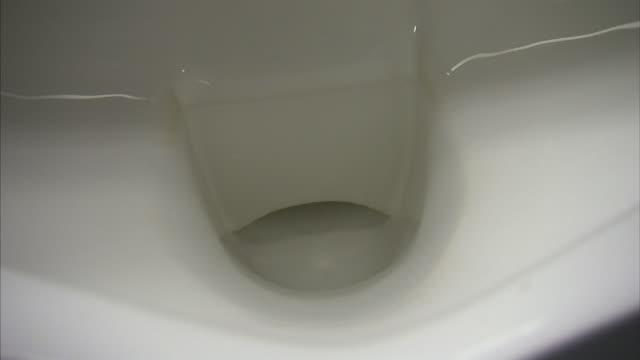 water fills a flushing toilet in a restroom. - 小便器点の映像素材/bロール