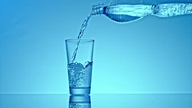 vídeos y material grabado en eventos de stock de slo mo agua de una botella de plástico en un vaso sobre un fondo azul suavemente iluminado - botella de agua