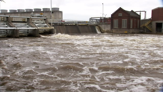 water flowing from dam rushing out into grand river power plants facilities across river bg mi hydroelectricity hydropower renewable energy - lansing stock videos and b-roll footage