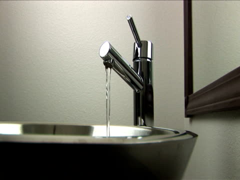 vidéos et rushes de cu, water flowing from faucet into sink - lavabo