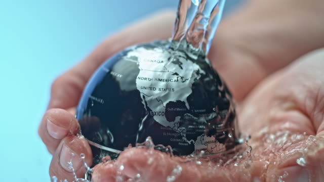 slo mo water flowing on top of a small globe being held in the person's hands - water conservation stock videos & royalty-free footage