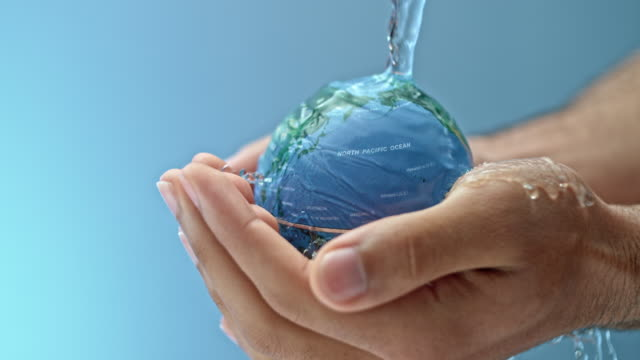 slo mo water flowing onto a small globe being held by a person - water conservation stock videos & royalty-free footage