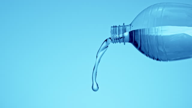 slo mo water flowing out of the plastic bottle opening - pouring stock videos & royalty-free footage