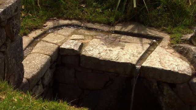 water flowing over stone wall in machu picchu, peru - stein baumaterial stock-videos und b-roll-filmmaterial