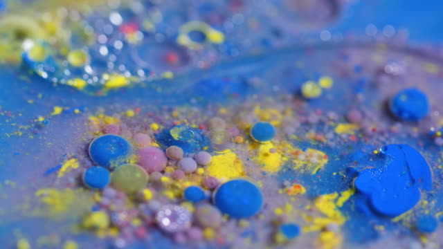 Water flows around vibrant blobs and flecks of paint in a shallow tray.