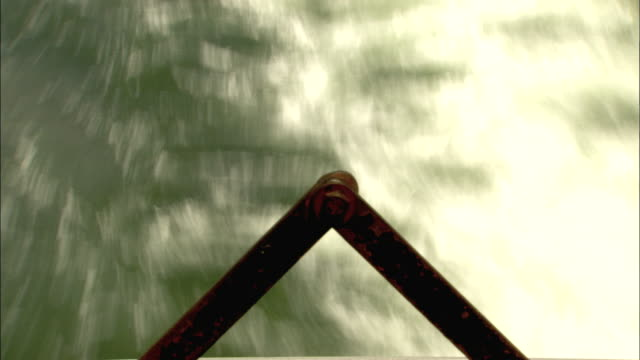 Water flows away underneath a triangular metal rod. Available in HD.