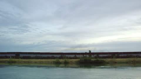 vídeos de stock, filmes e b-roll de a água flui por um canal correndo paralelamente ao muro da fronteira aço-slat (no lado dos eua) entre o méxico e os estados unidos em um dia parcialmente nublado ao pôr do sol - caniço