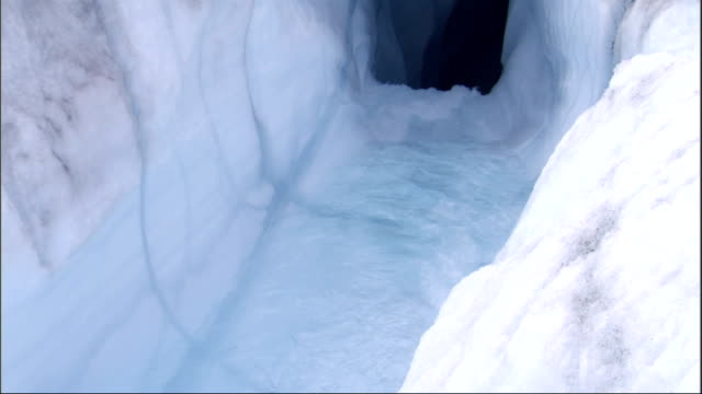Water flows down an ice gully into a cavern. Available in HD.