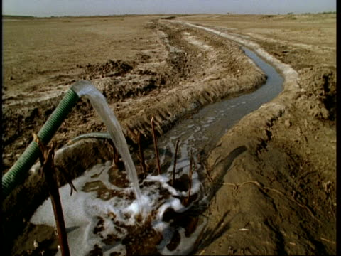 ms water flows from pipe into water-course in desert, gujarat, india - グジャラート州点の映像素材/bロール