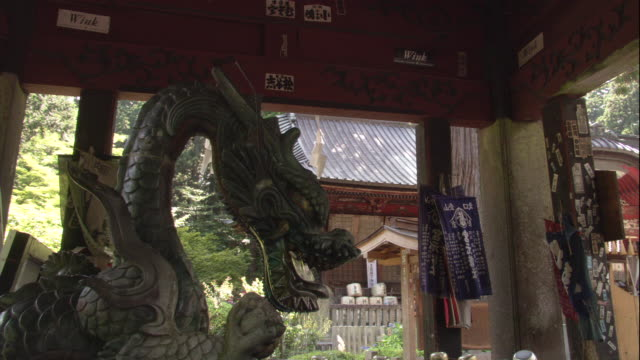 water flows from the mouth of a dragon fountain into a pool at a shinto shrine. - temple building stock videos & royalty-free footage