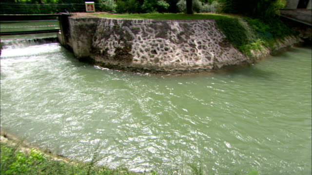 water flows in a canal beside a pumping station. - water pumping station stock videos & royalty-free footage