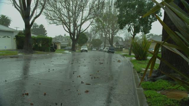 wide pan water flows in gutter during heavy rain on suburban street - santa barbara california stock videos & royalty-free footage