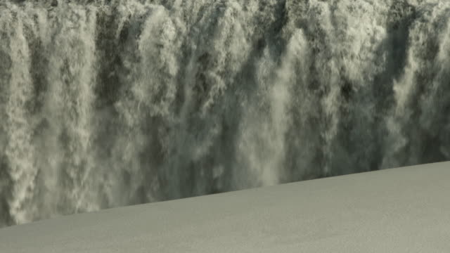 water flows over a large waterfall in iceland.  - dirty stock videos and b-roll footage