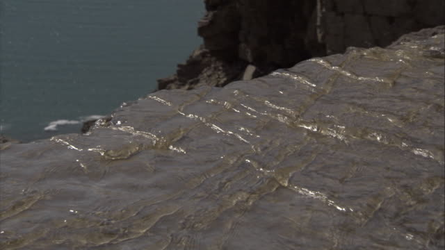 """vidéos et rushes de water flows over a rocky cliff to the coast at cunningham inlet. - """"bbc natural history"""""""