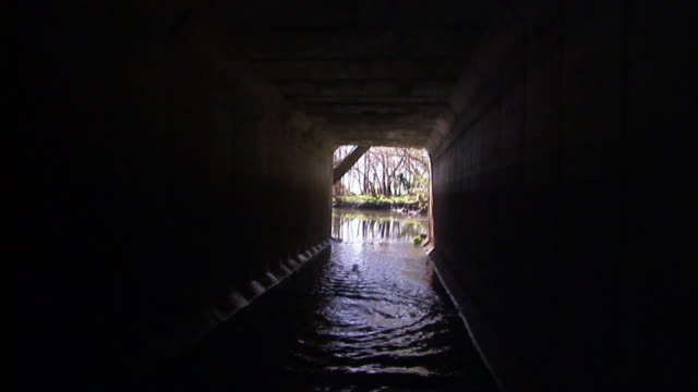 Water flows through a tunnel which emerges into a quiet stream.