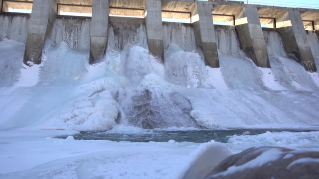 water flows through frozen dam - hydroelectric power stock videos & royalty-free footage