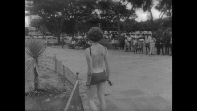 water fountains in the center of salisbury rhodesia / local women sitting in a circle on the ground / model in skimpy swim suit lies on wall of water... - full suit stock videos & royalty-free footage