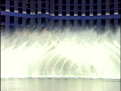 Water fountains spray to left and right and raise up and down in impressive display outside Bellagio casino lights make evening sky look blue Las Vegas