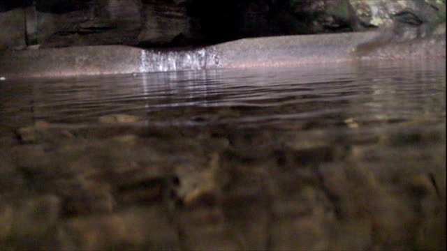 water from a cave pours over a ledge into a clear pond. - transparent stock videos & royalty-free footage