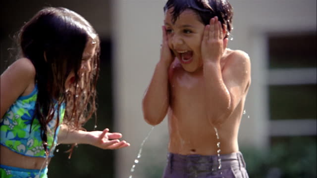 water from a hose splashes down on a brother and sister in their bathing suits. - swimwear stock videos and b-roll footage