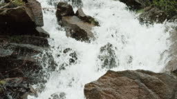 Water from a Mountain Stream Falls over Rocks and Boulders in Slow Motion