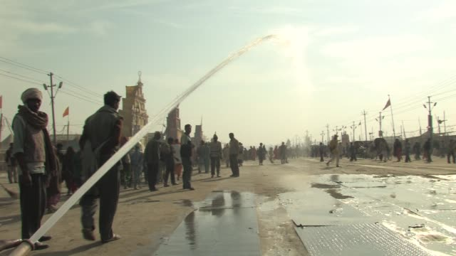 stockvideo's en b-roll-footage met ws, water from fire hose being shot out onto wide street with people around, allahabad, uttar pradesh, india - fire hose