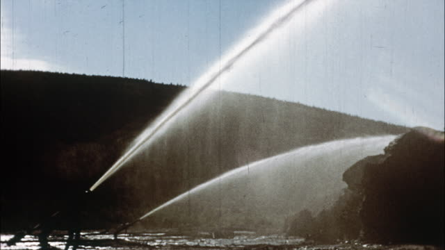 Water from large hoses spray away permafrost in a gold field; a steam shovel lifts dirt; a worker works on a conveyor belt carrying dirt; a prospector pans for gold in a stream; a large conveyor pans for gold.
