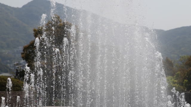 Water geysers and mountain landscape in the background of the Fountain of Peace at the Nagasaki Peace Park located on the grounds of the hypo center...