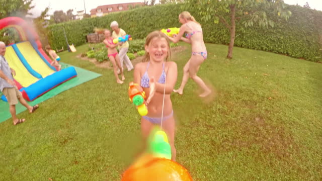 pov water gun fight at a children's party - water slide stock videos & royalty-free footage