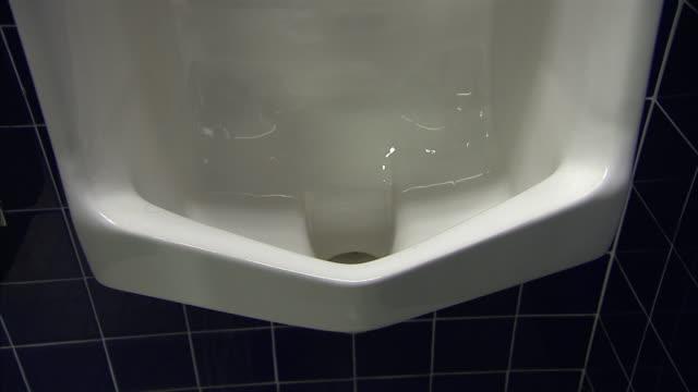 water gurgles in a public urinal. - 小便器点の映像素材/bロール