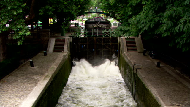 water gushes out of a canal lock in paris. - chiusa di fiume video stock e b–roll
