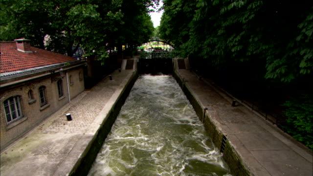 water gushes through a canal lock in paris. - chiusa di fiume video stock e b–roll