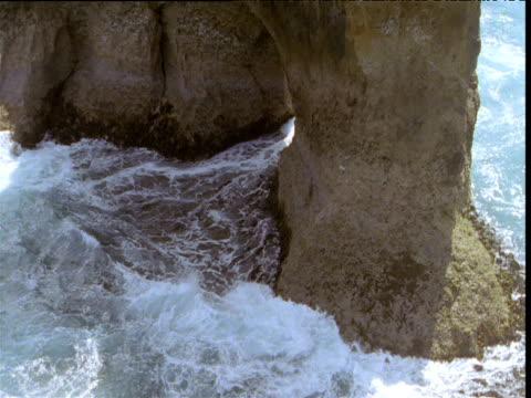 Water gushes through rock arch at Twelve Apostles, Victoria, Australia