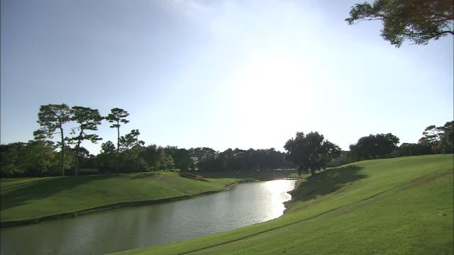 vídeos de stock, filmes e b-roll de a water hazard abuts a fairway on a golf course. - obstáculo de água