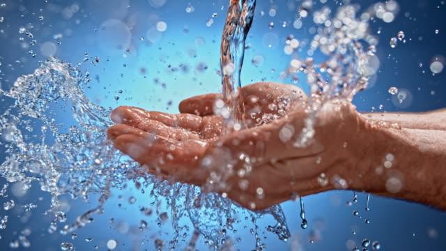 slo mo ld wasser stark gießt mann hände halten offene handflächen - erfrischung stock-videos und b-roll-filmmaterial
