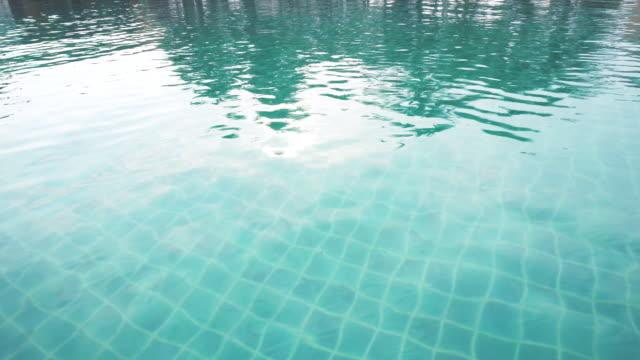 vidéos et rushes de l'eau dans le bleu profond d'aqua avec la vague ondulée dans la piscine d'hôtel pour des vacances de plage d'été ou le fond de partie de piscine - station de vacances