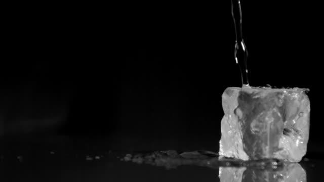 vidéos et rushes de water in super slow motion falling on ice cubes - glaçon