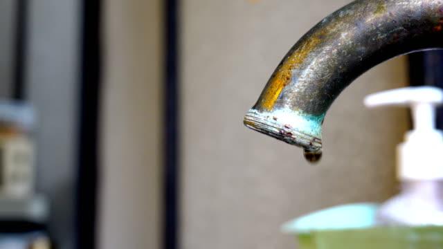 vídeos y material grabado en eventos de stock de el agua gotea de un grifo de cocina - agua del grifo