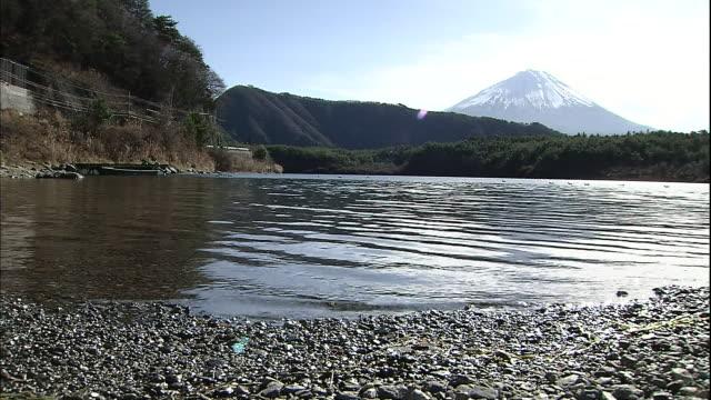 Water laps the shore of Lake Saiko in the Fuji Hakone Izu National Park in Yamanashi, Japan.