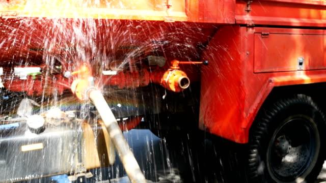 vídeos de stock, filmes e b-roll de vazamento de um conector de mangueira de incêndio caminhão de água - vazamento
