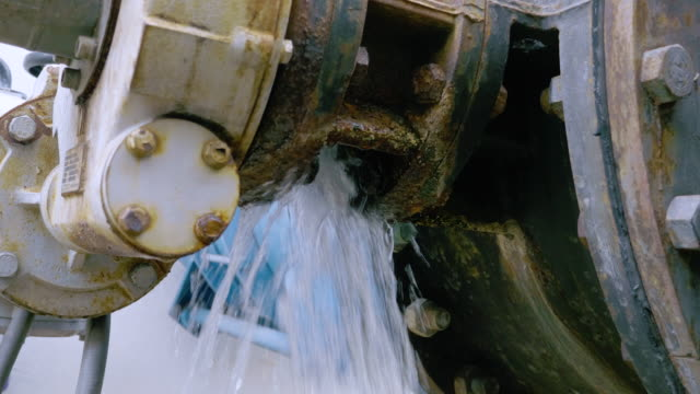 water leaking from connection of valve and pipe at waste water at sewage treatment plant. - leaking stock videos & royalty-free footage