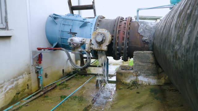 water leaking from connection of valve and pipe at waste water at sewage treatment plant. - rusty stock videos & royalty-free footage