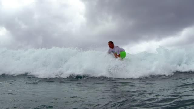 water level shot of a surfer jumping onto his board and riding right towards camera - タートル湾点の映像素材/bロール