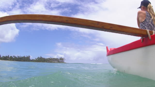 water level shot of outrigger passing by camera - タートル湾点の映像素材/bロール